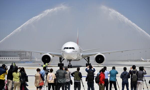 """5月3日,阿联酋航空波音777飞机抵达银川河东国际机场,通过欢迎仪式上的""""水门""""。当日13时35分,阿联酋航空—架波音777飞机降落在银川河东国际机场,阿联酋航空迪拜经银川至郑州航线正式开通。新华社记者 王鹏 摄  5月3日,在银川河东国际机场,群众载歌载舞欢迎来宾。新华社记者 王鹏 摄  5月3日,来自阿联酋的旅客抵达银川河东国际机场。新华社记者 王鹏 摄"""